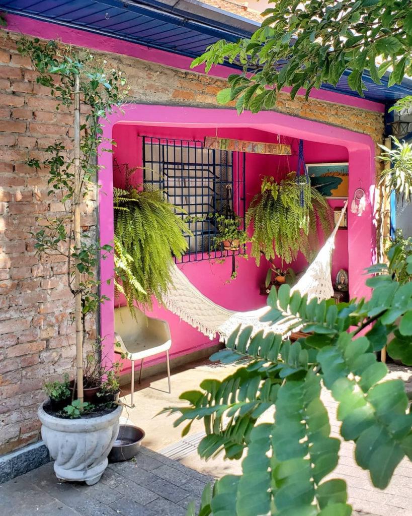 Cor-de-rosa foi a escolha para a parede dessa casa com tijolinhos e janela azul.