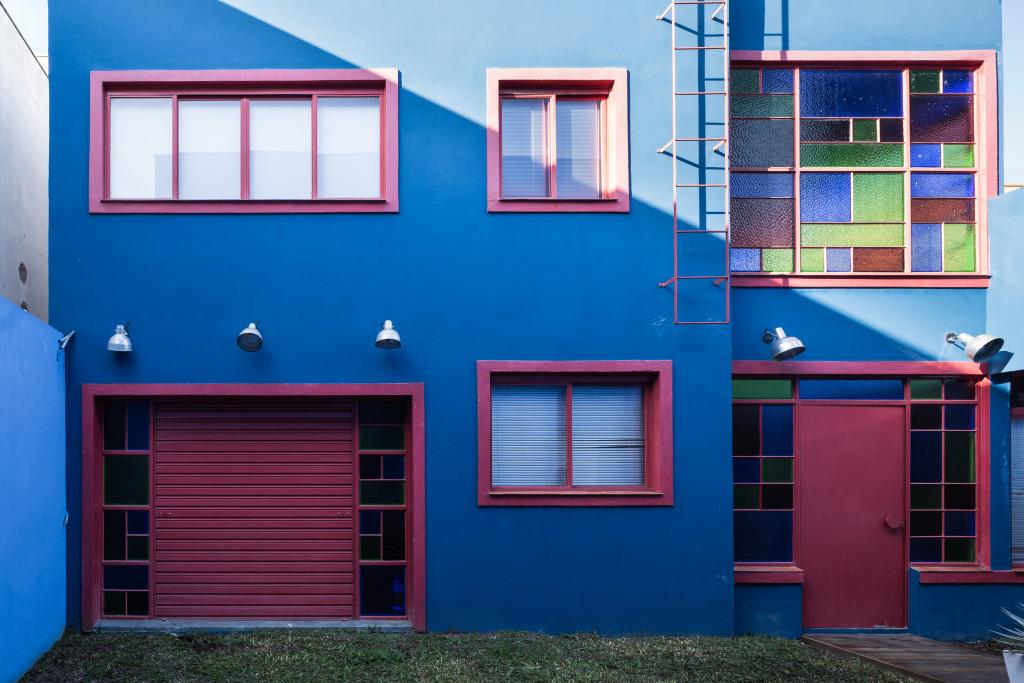 Fachada de casa em azul com janelas vinho.