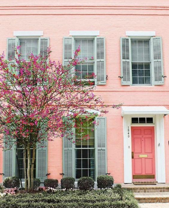 Fachada de casa em rosa com janelas azul-claro.
