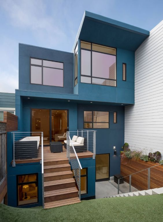 Fachada em azul com janelas em caixilhos pretos.