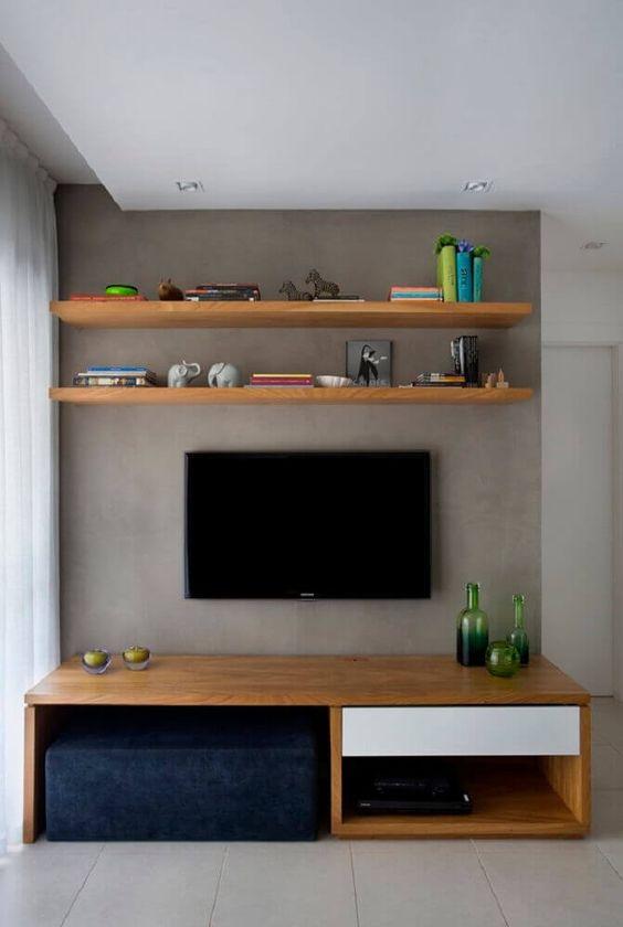 parede cinza, rack com estantes de madeira e decoração simples.