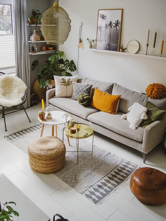 Sala com paredes brancas, sofá cinza, almofadas amarelos e verde, pufes e tapedes geométricos.