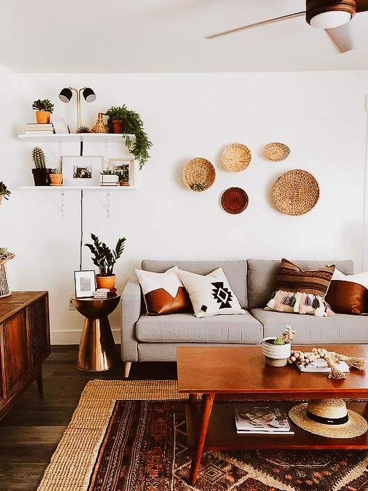 Sala decorada com diferentes texturas nas almofadas, tapete e decoração na parede.