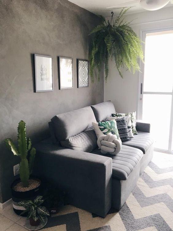 Sala com parede de cimento queimado, sofá cinza e plantas.