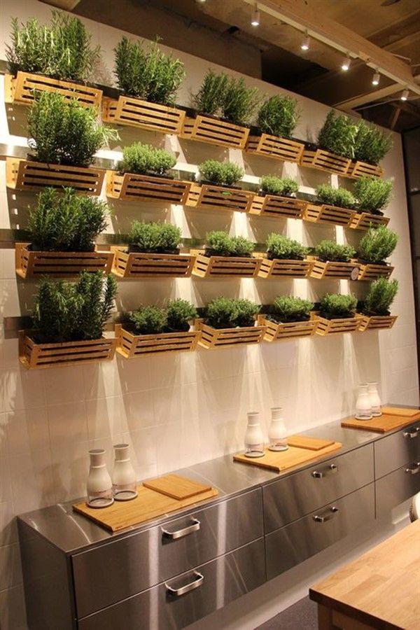 Cozinha com decoração elegante e horta vertical com caixotes.