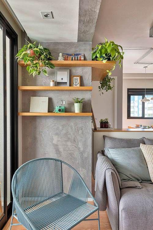 Estante de madeira em três níveis, decorada com plantas, quadros e objetos de decoração.