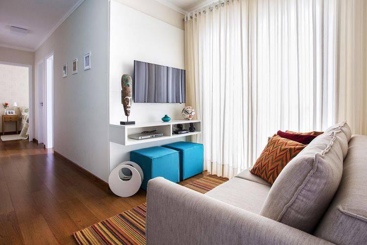 Sala simples, com cortina leve, sofá cinza. rack branco e pufes azuis.