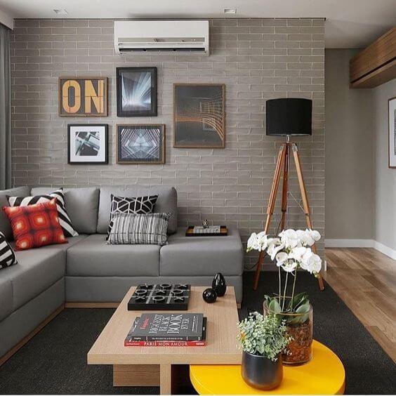Sala decorada com paredes e sofá cinzas e quadros, almofadas e mesa de centro coloridos.
