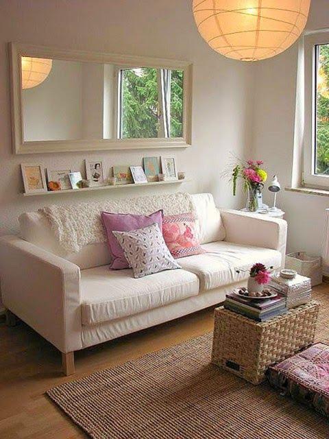 Decoração com espelho retangular em cima do sofá