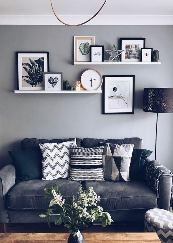 Sala decorada com estante com quadros e objetos decorativos;