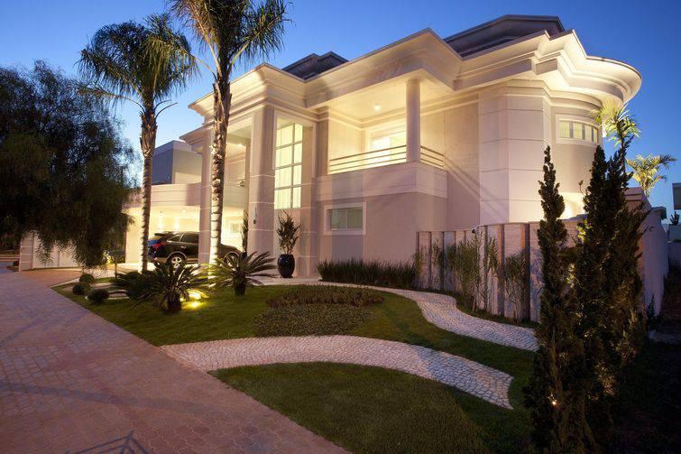 Casa de dois andares e arquitetura sofisticada, com fachada clara e jardim na frente