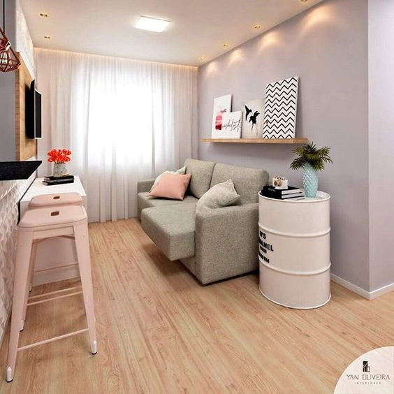 Sala com paredes e sofá cinzas, almofadas e bancos rosa bebê e chão de madeira.