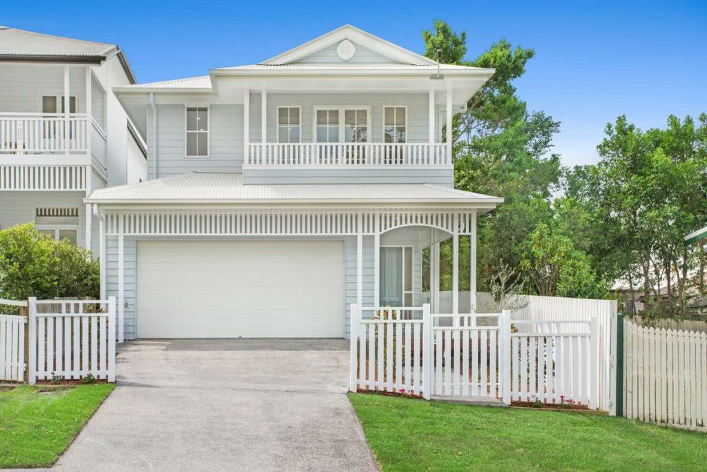 Casa com fachada cinza e cerca branca, no estilo americano.