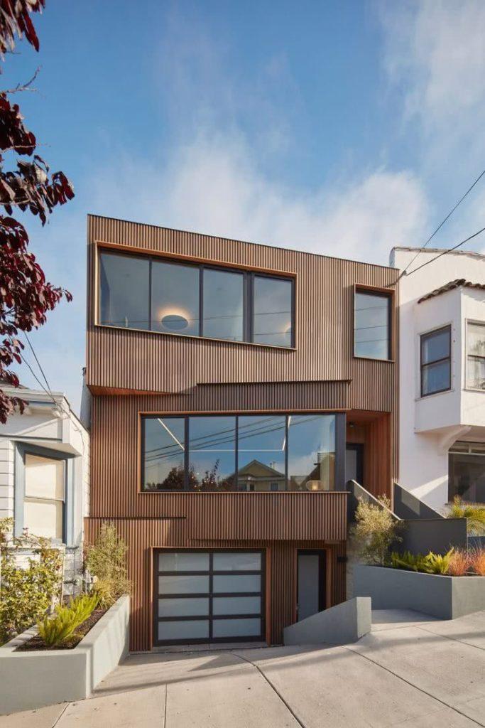 Casa de três andares com fachada de madeira.