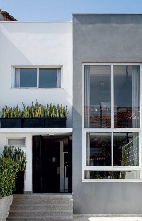 Casa cinza e branca, construída com linhas retas.