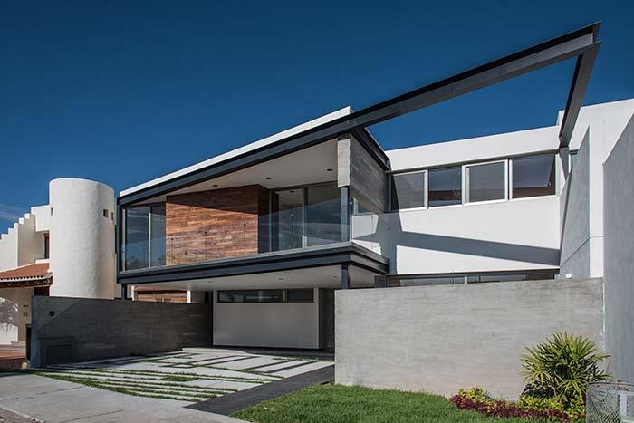 Casa de dois andares, com arquitetura moderna e viga de ferro na fachada.