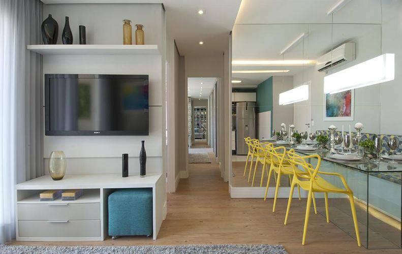 Espelho grande, mesa de vidro com cadeiras amarelas, rack branco com TV e pufe azul.
