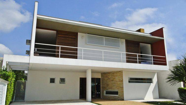 Modelo de casa moderna, com grande varanda na fachada e mistura de elementos.