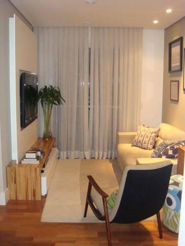 Sala decorada com rack de madeira, sofá bege, uma poltrona e almofadas em tons de azul.