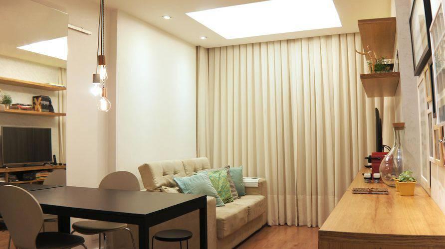 Sala decorada com rack de madeira, sofá befe, mesa de jantar preta, duas cadeiras e luminária moderna,