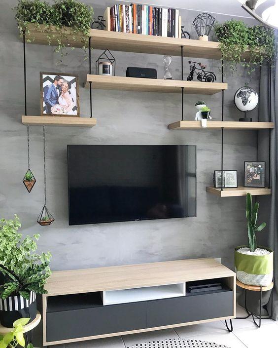 Sala com parede cinza e estante de madeira clara em vários níveis, decorada com plantas e objetos.