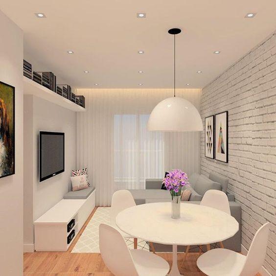 Comodo todo branco, com uma parede de tijolos, mesa de jantar, rack, luminária e um sofá cinza.