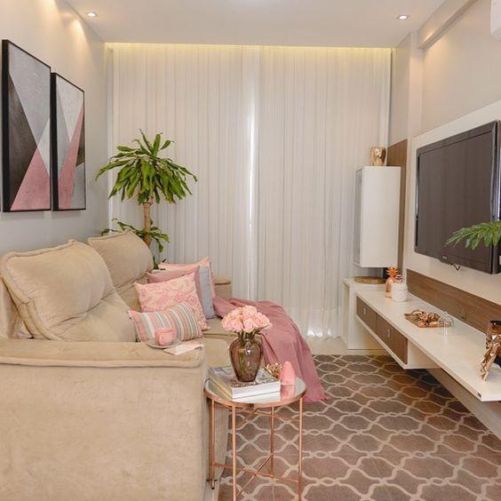 Sala clean, decorada com sofá bege, almofadas e manta rosas e rack branco, com madeira.