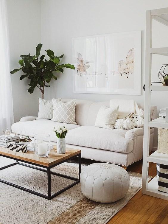 Sala decorada no estilo minimalista, usando o branco, linhas retas e madeira. Conta com uma planta no canto.