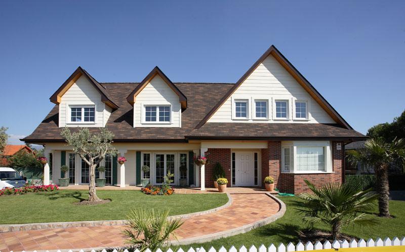 Modelo de casa tradicional, no estilo americano, cm dois andares e janelas no telhado.