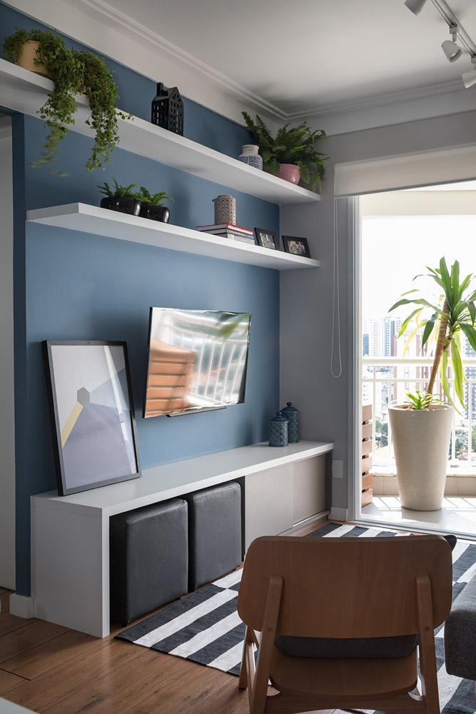 Parede azul e estante branca, plantas e objetos decorativos e dois pufes, armazenados embaixo dela.