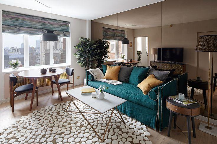 Espelho grande atrás do sofá verde. Em cima do sofá, almofadas amarelas, verdes e cinzas.