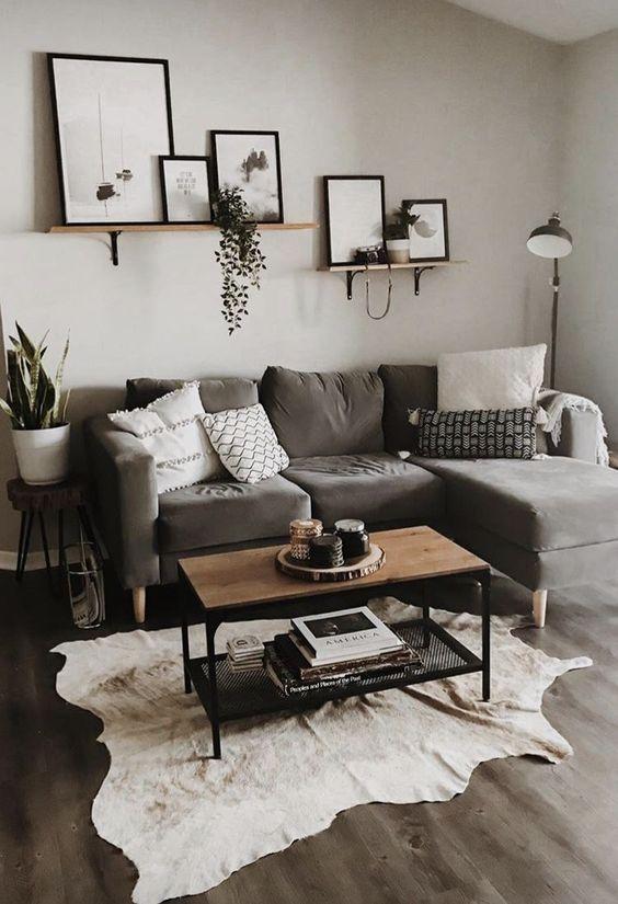 Sala com paredes e sofás cinza e duas prateleiras de madeira, decoradas com quadros e plantas. Em cima do sofá tem almofadas pretas e brancas e em frente tem uma mesa de centro de madeira, com um tapete branco embaixo.