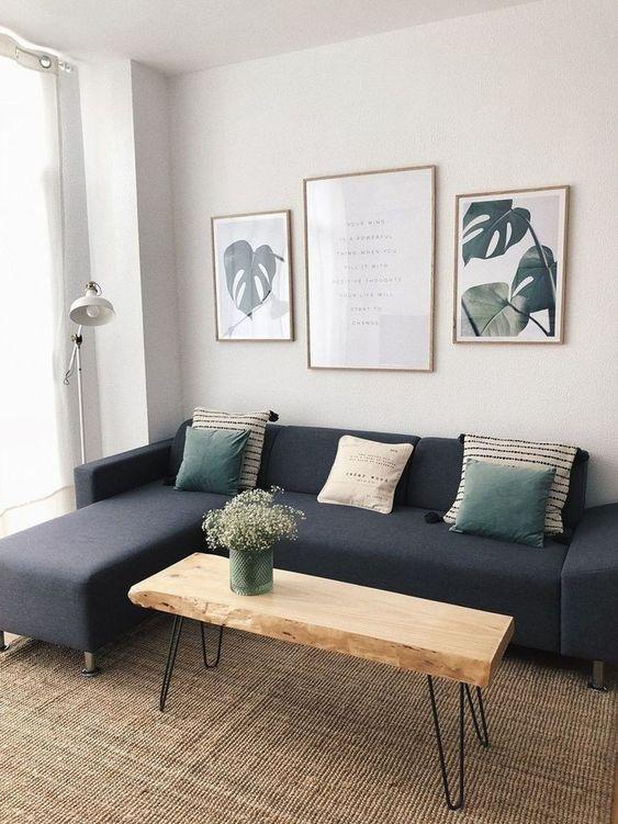 Sala com sofá azul, paredes claras com três quadros grandes. Uma mesa de centro de madeira e um tapete de sisal completam o ambiente.