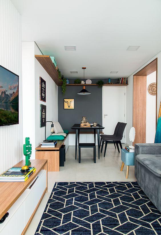 Sala branca, com uma parede escura, rack de madeira e sofá cinza. O tapete é preto e branco, com desenho geométrico.