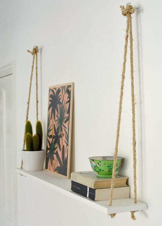 prateleira branca, com suportes de corda, decorada com quadros, plantas e livros.
