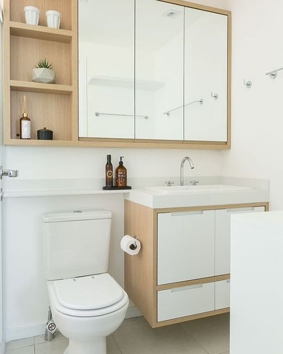 Banheiros modernos com madeira clara.