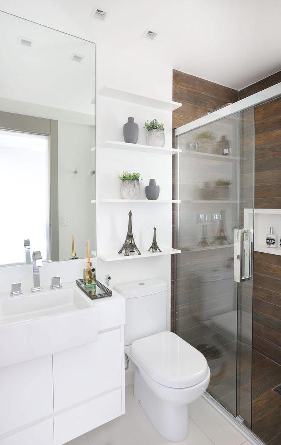 Prateleiras armazenam itens decorativos no banheiro moderno.