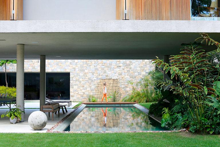 Casa moderna com paisagismo traz integração entre urbano e a natureza.