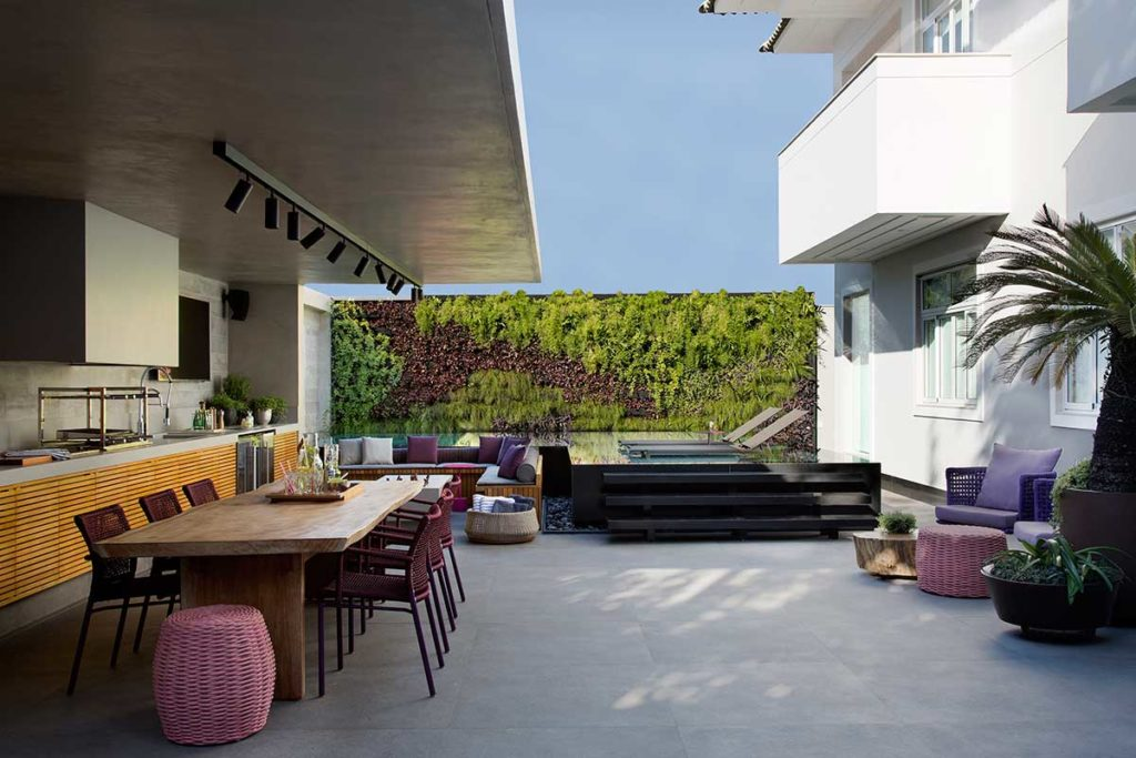 Piscina em deck, jardim vertical e porcelanato que imita cimento queimado