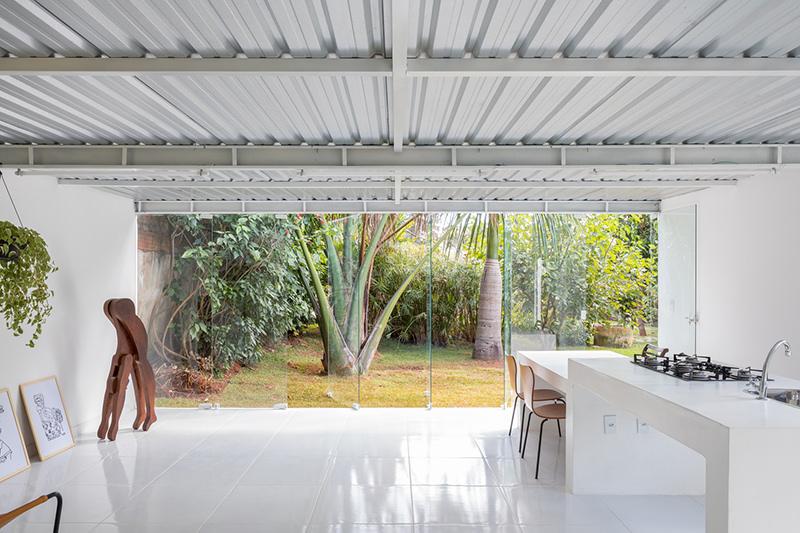 Casas modernas pequenas como essa trazem tons claros e vidro que permite a luz entrar.