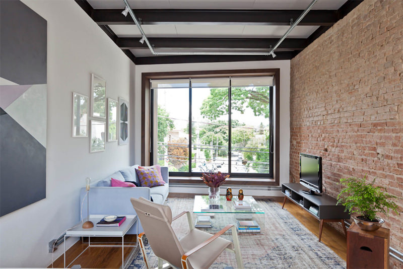 Trio perfeito: tijolos aparentes, caixilhos pretos e trilhos de luz.