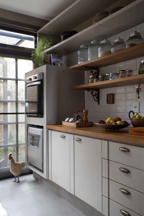 Cozinha moderna com prateleiras e eletrodomésticos embutidos.