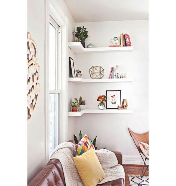 Estante em canto da parede decorada com plantas, livros, quadros e objetos.