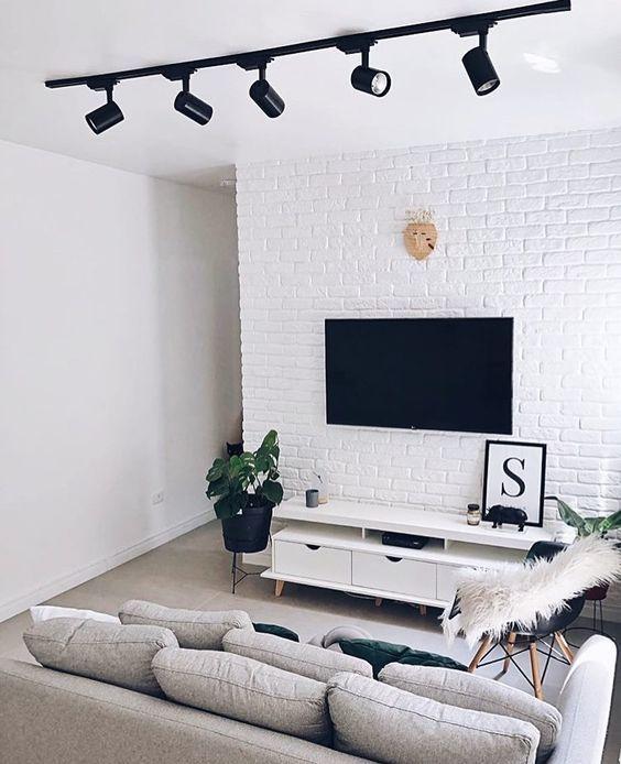 Sala toda branca, decorada com sofá cinza e móveis brancos.