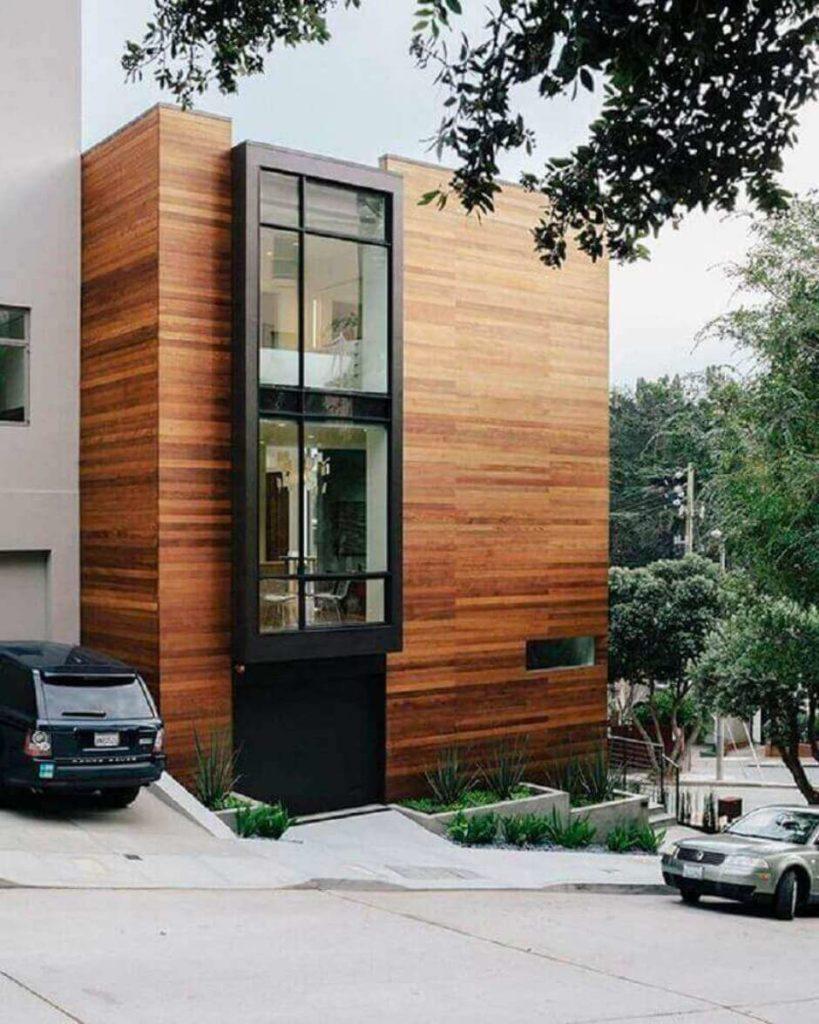 Casa de dois andares, com fachada toda de madeira e metal.