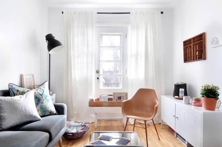Sala com piso de madeira, parede branca, sofá cinza e móvel branco.