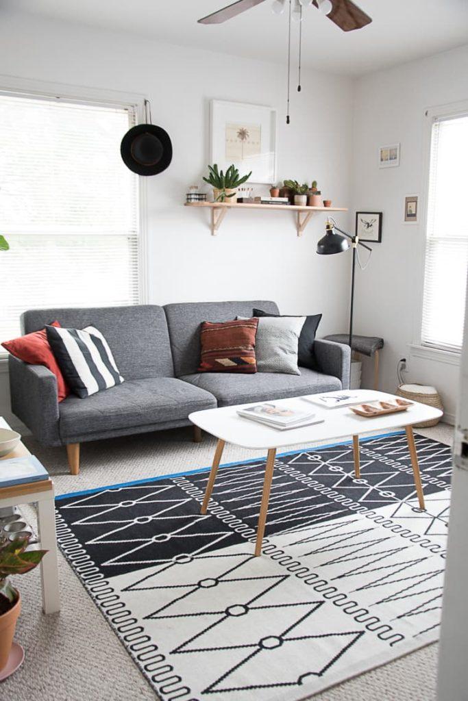 Sala branca, com mesa de centro da mesma cor, tapete geométrico e sofá cinza.