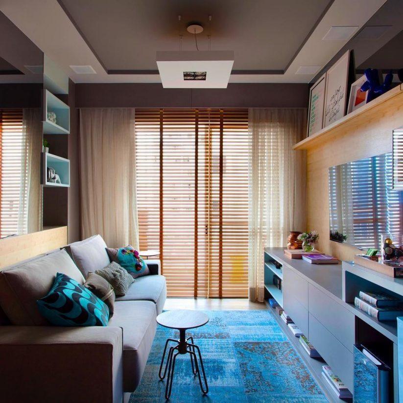 Sala com tapete azul, sofá e rack azul e tom de madeira clara. As almofadas são cinzas e azuis.