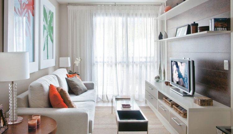 Sala com sofá branco, tapete bege, rack branco com painel de madeira e quadros grandes atrás do sofá.