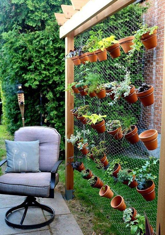 Jardim vertical pequeno feito com tela de galinheiro e vasos de barro.